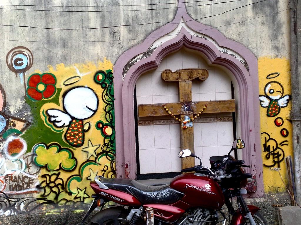 A typical bandra corner housing a cross contrasted with fresh graffiti ©Flickr/Satish Krishnamurthy