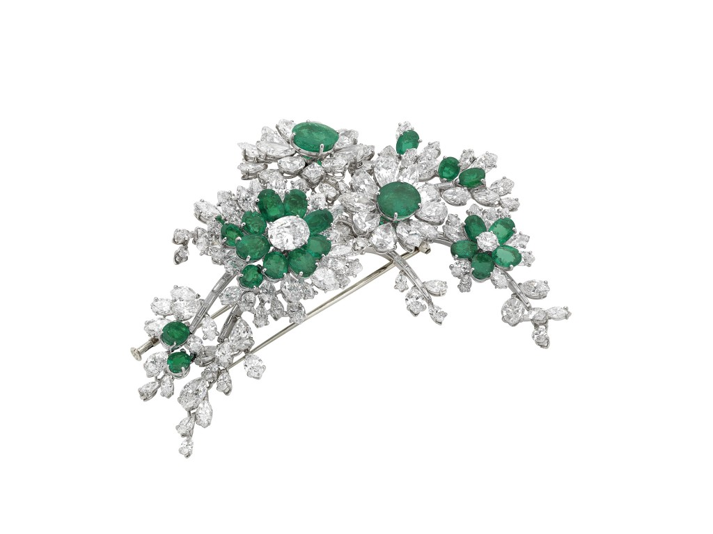 """Tremblant"" brooch in platinum with emeralds and diamonds, 1960. The brooch was probably given to Elizabeth Taylor by Eddie Fischer, her husband at the time and was worn both as a brooch and hair ornament. On the ""tremblant""pieces, flowerheads are mounted on spring settings which allow them to flicker at every movement, thus marvelously radiating their light. Since the 18°  century, realistic floral motifs had been a constant theme in French jewellery. In the early 1960s, Bulgari rivalled the finest Parisian jewellers in creating these asymmetrical sprays. Marks: on the clip mechanism: mark (illegible legible); ""DEPOSÉ""."