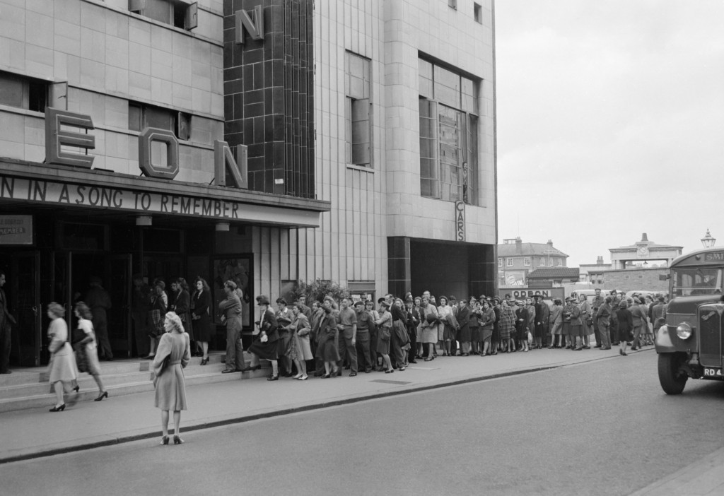 A long queue stretches out from the entrance of the Odeon Cinema in wartime Reading, as people buy tickets, 1945|©© IWM (D 25326) /IWM