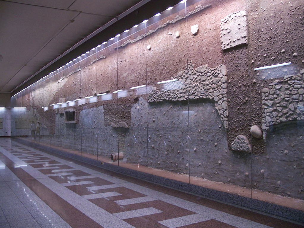 Stratigraphy of the antiquities wall of Athens Metro Syntagma station, with the pipe in the center belonging to the Peisistratid aqueduct. | © Badseed/WikiCommons