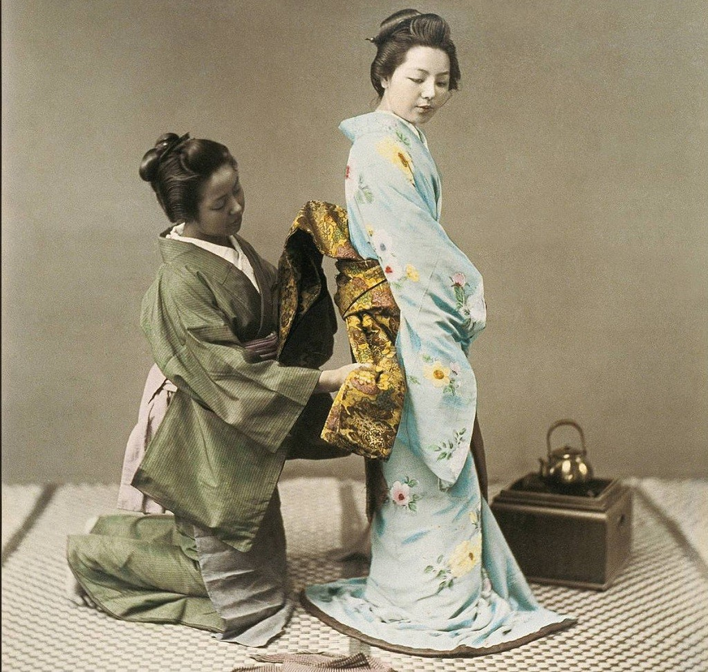 A geisha gets help with her obi | © The Burns Archive/WikiCommons