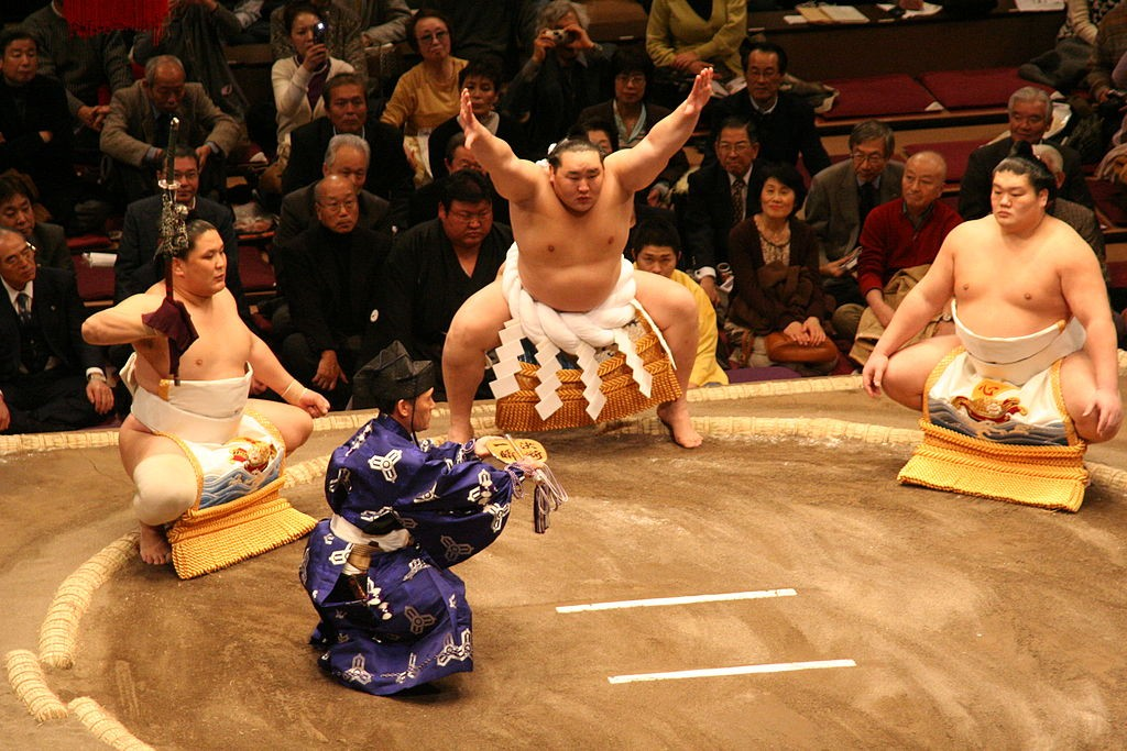 Another wrestler acts as tachimochi (sword bearer) during the yokozuna Asashōryū's ring entrance ceremony. Tachimochi is only for wrestlers who have achieved yokozuna rank | © Eckhard Pecher/WikiCommons