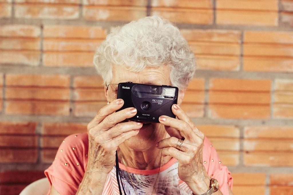 An elderly woman poses with her camera   © Tiago Muraro/Unsplash
