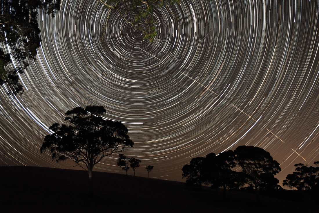 'Just Missed the Bullseye' by Scott Carnie-Bronca.The International Space Station (ISS) appears to pierce a path across the radiant, concentric star trails seemingly spinning over the silhouettes of the trees in Harrogate, South Australia|©Scott Carnie-Bronca/Royal Observatory Greenwich