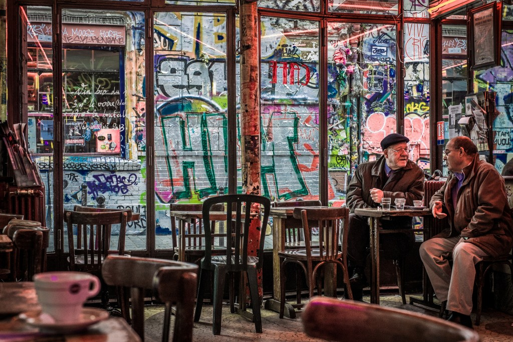 Two men drinking coffee in a Paris café with graffiti outside the window │© Willy Verhulst