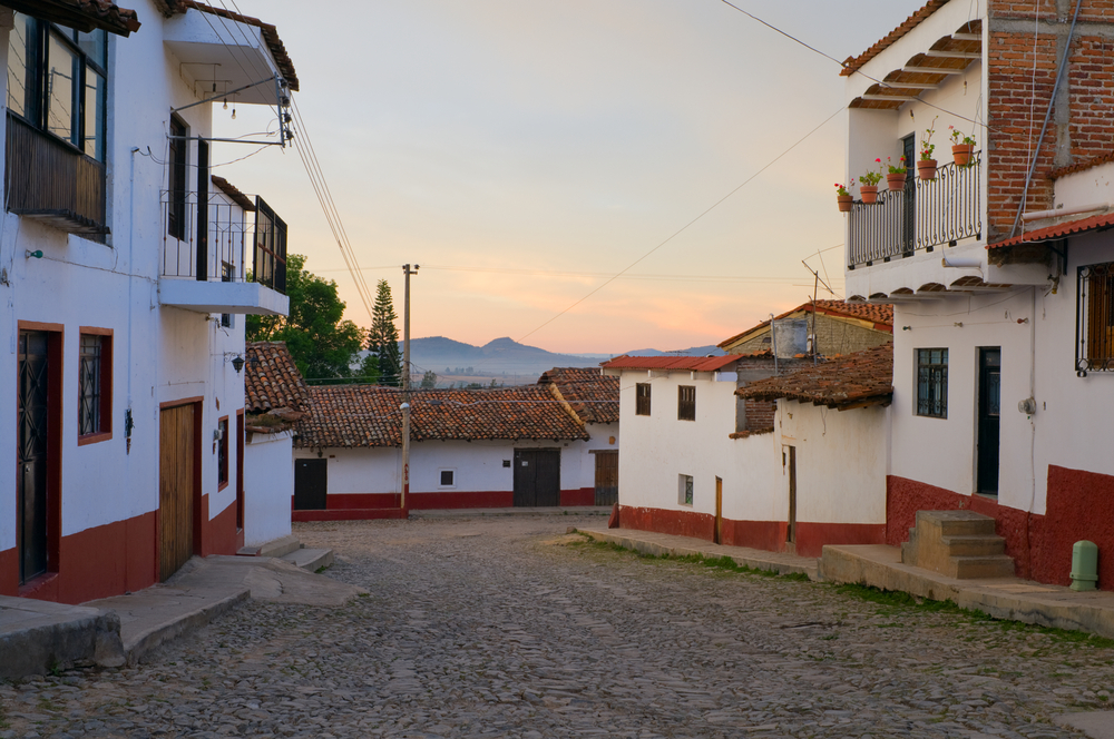 Cobblestone streets of alpine village Tapalpa in Mexico with mountains on horizon at daybreak © Joe Ferrer / Shutterstock