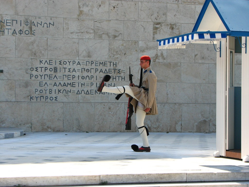 An evzone lifts his leg up to shoulder height   © fdecomite/Flickr