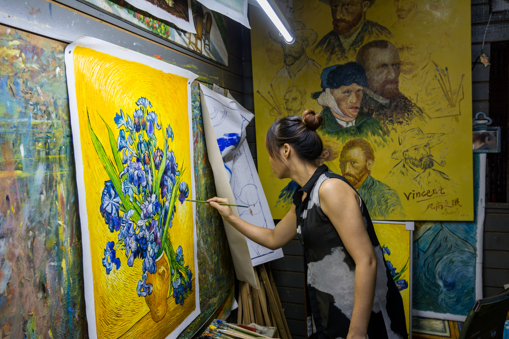 A female painter painting a Vincent van Gogh's famous masterpice in her studio in Dafen| © Victor Jiang/Shutterstock