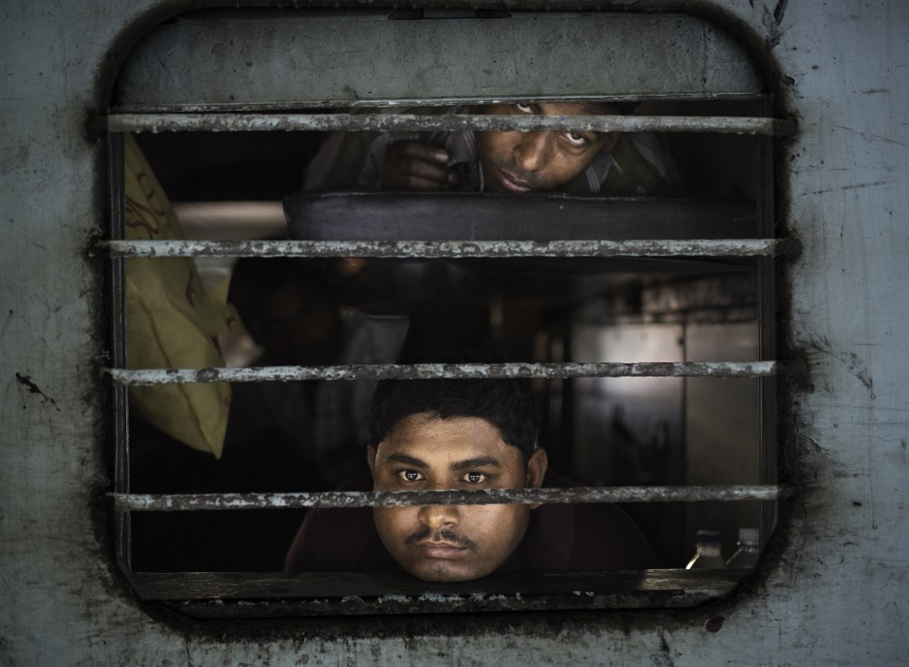 Marco Pozzi, Men peering out from a train, Jaipur, India