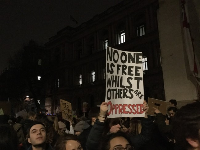 """A protester holds a sign aloft: """"No one is free whilst others are oppressed."""" 