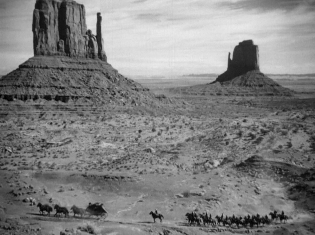 Travelers dwarfed by Monument Valley's East and West Mittens in 'Stagecoach'   © United Artists