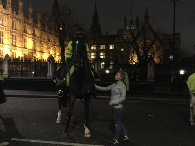 Protester Millie Pellowe takes a moment to befriend a police horse outside Westminster station | © Ruaidhrí Carroll