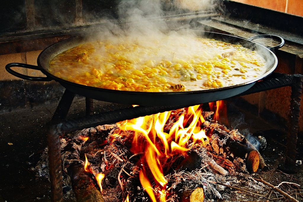 Valencian paella cooking over firewood. © Wikimedia Commons