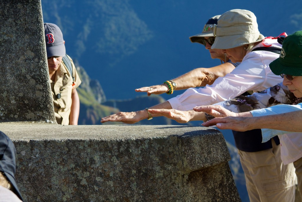 Tourists place their hands as close as possible to the Intihuata rock to channel energies.   © McKay Savage/Flickr
