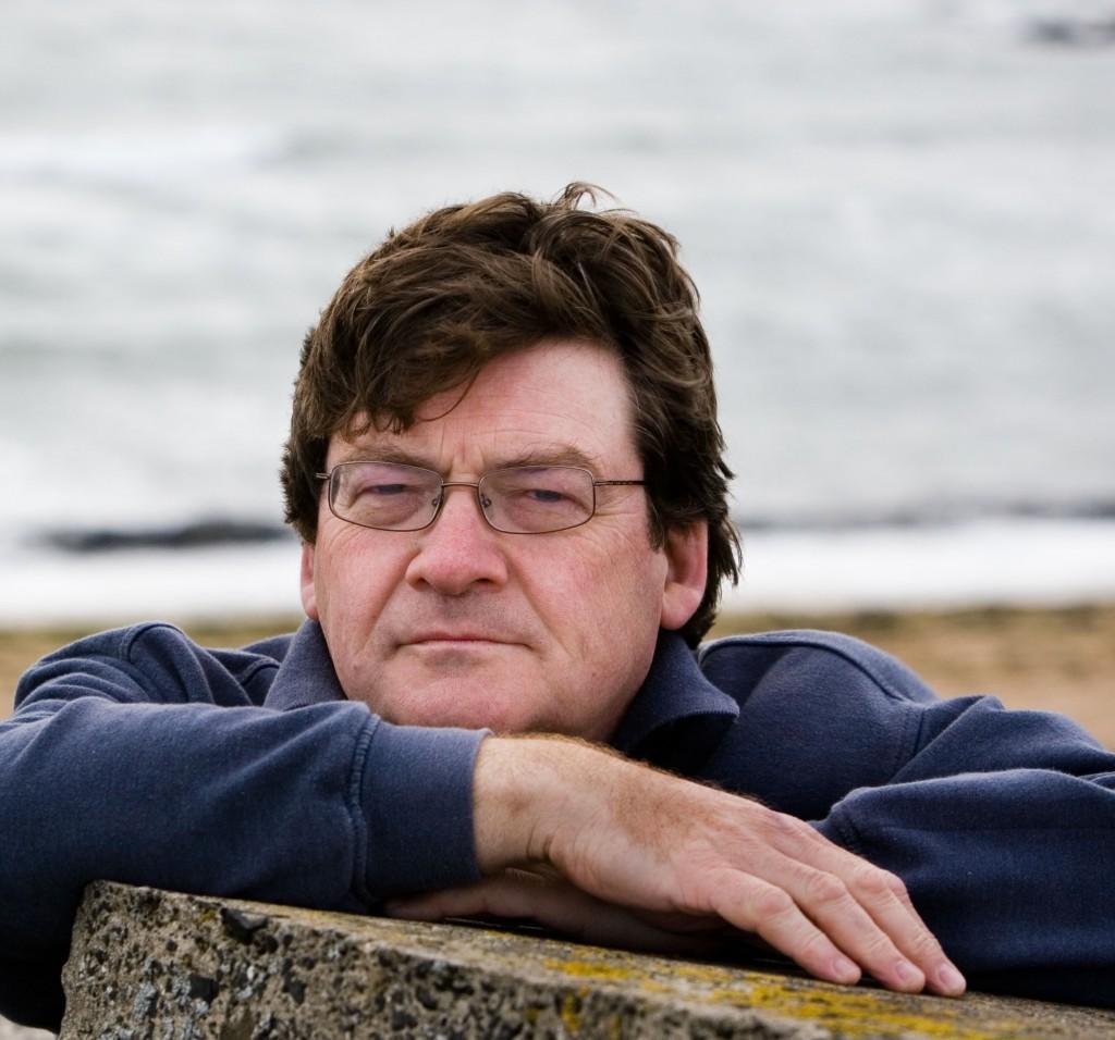 John Burnside, ein schottischer Autor sitzt an einer Landzuge Landschaft in der sich wie in seinen Romanen, Niedergang, Furcht, Krankheit und Tod angesiedelt haben kˆnnen, die Bucht befindet sich bei Anstruther einem ehemaligen Fischerdorf 80 km Nˆrdlich non Edinburgh am Montag den 28 September 2009.
