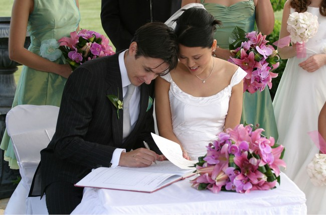Wedding signatures | ©Jason Hutchens / Wikimedia https://commons.wikimedia.org/wiki/File:Bride_and_groom_signing_the_book.jpg