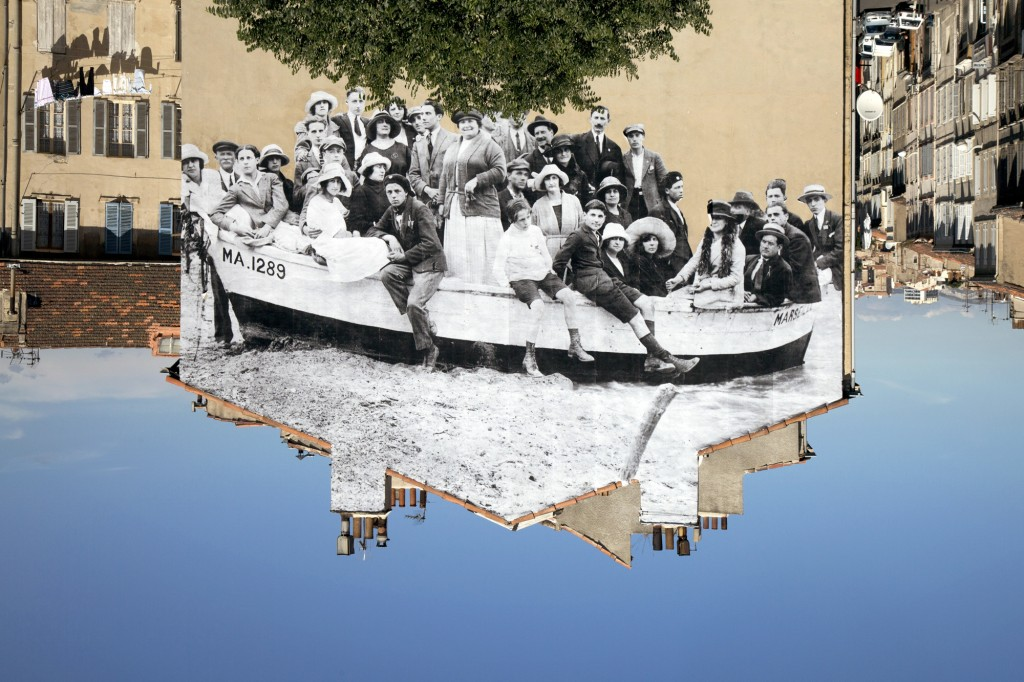 """UNFRAMED, a group posing in a bark moored on the beach, reviewed by JR, circa 1930, Marseille, France © JR-ART.NET / Courtesy Galerie Perrotin"