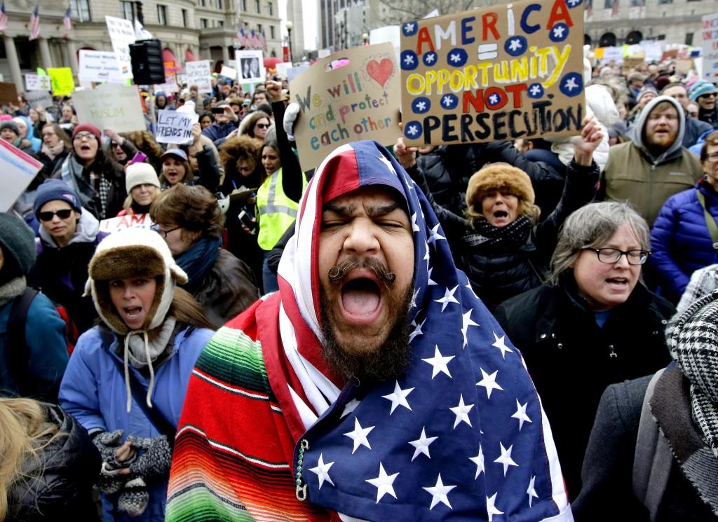 Izzy Berdan, of Boston, center, wears an American flags as he chants slogans with other demonstrators ©AP/REX/Shutterstock