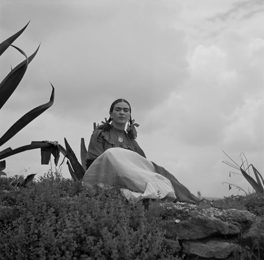 """Frida Kahlo, seated next to an agave plant, from a 1937 photo shoot for Vogue entitled """"Señoras of Mexico"""". 