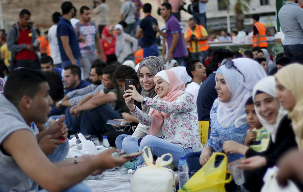 "Women take a ""selfie"" as people gather to eat their Iftar (breaking of fast) during a local initiative called ""Let's Have Iftar Together"" during the holy fasting month of Ramadan in Amman, Jordan June 27, 2015. © Muhammad Hamed, Reuters"