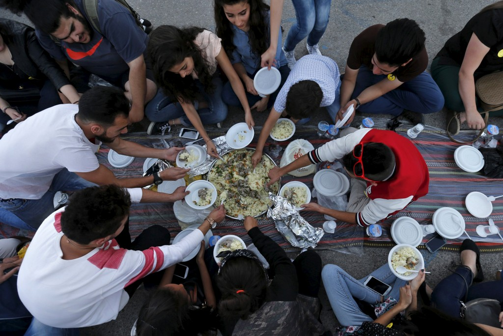 "People eat their Iftar (breaking of fast) during a local initiative called ""Let's Have Iftar Together"" during the holy fasting month of Ramadan in Amman, Jordan June 27, 2015. © Muhammad Hamed, Reuters"