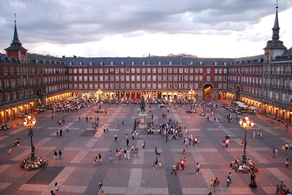 "<a href=""https://simple.wikipedia.org/wiki/Plaza_Mayor_of_Madrid#/media/File:Plaza_Mayor_de_Madrid_06.jpg""> The Plaza Mayor at dusk 