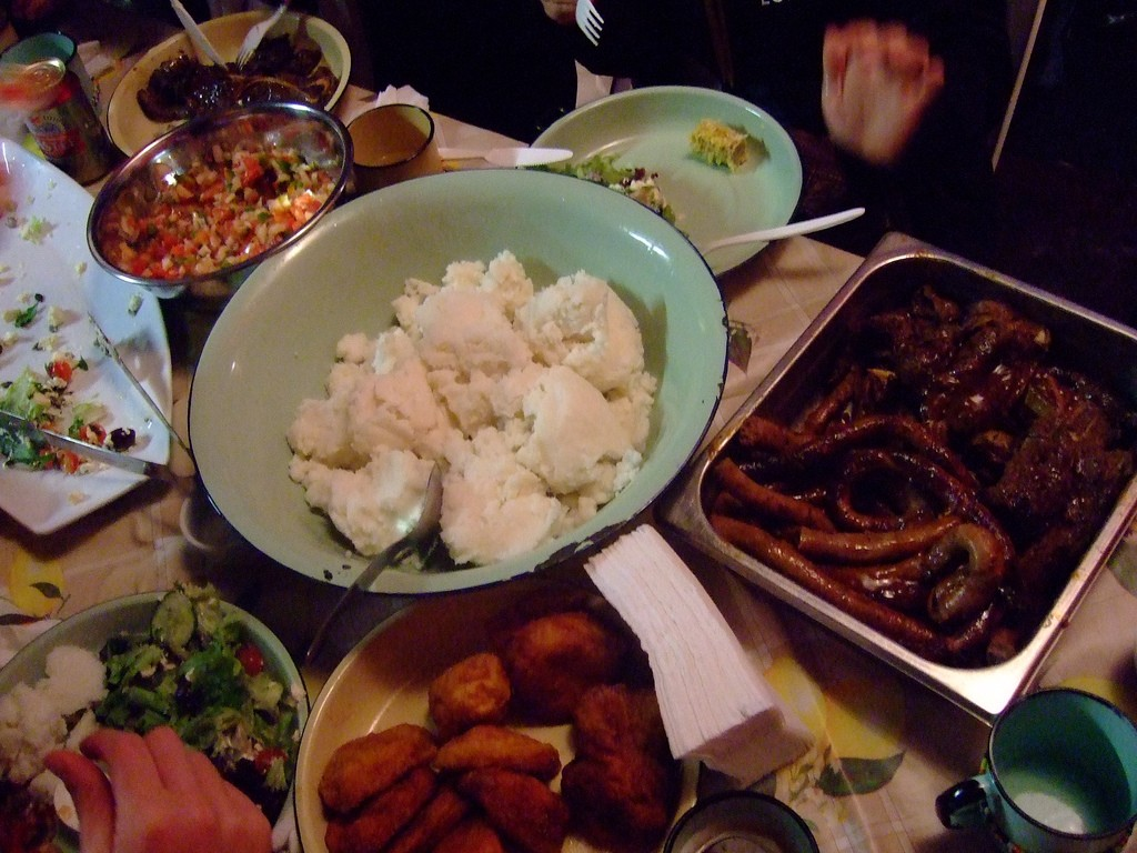 A delicious spread of braai meat, pap and salads at Mzoli's Place © Yosoynuts/Flickr
