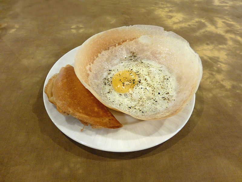A crispy egg hopper sprinkled with salt and pepper ready to be devoured.| ©Wikimedia Commons