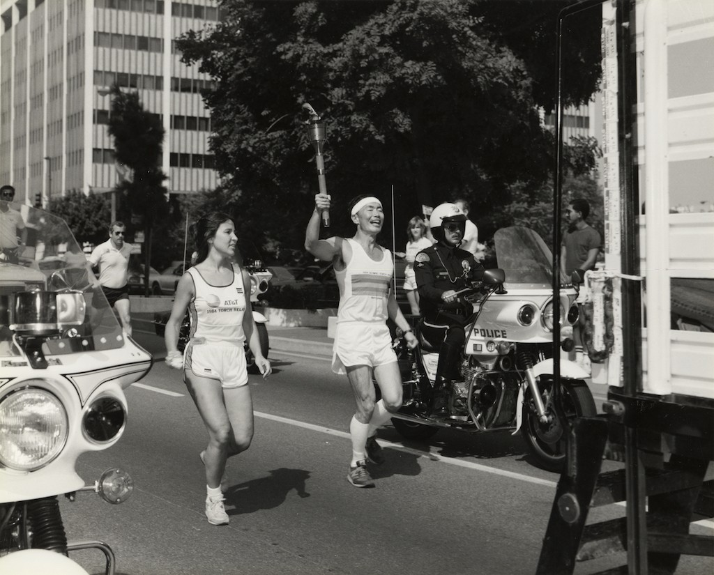 George Takei carries the Olympic torch through the streets of Los Angeles in the run up to the 1984 Olympic Games|George & Brad Takei Collection, Japanese American National Museum