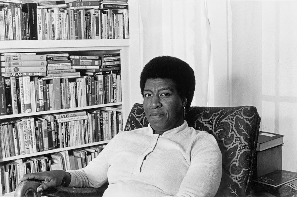Octavia E. Butler seated by her bookcase, 1986. Photo by Patti Perret|The Huntington Library, Art Collections, and Botanical Gardens