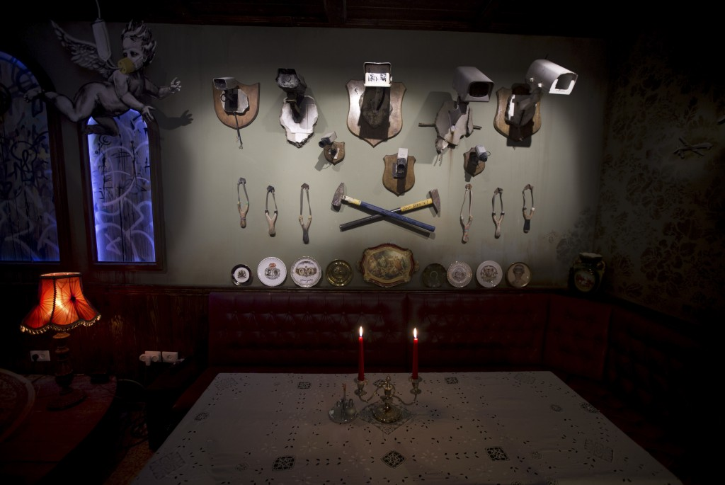 "Wall decorated with security cameras and slingshots is seen in the bar area of the ""The Walled Off Hotel"" and the Israeli security barrier in the West Bank city of Bethlehem 