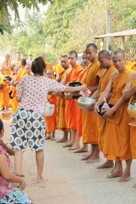 Making merit by giving alms to monks | © thanavut/Depositphotos