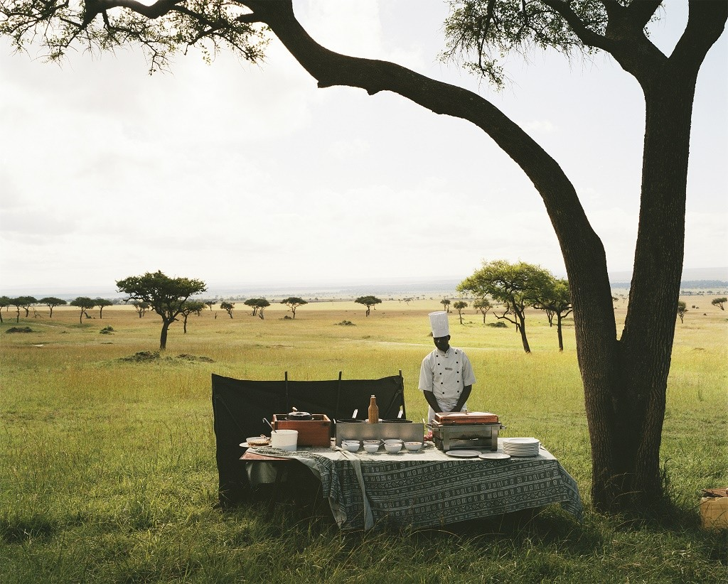A chef from a nearby luxury lodge waits for his guests to arrive from a hot air balloon excursion before serving them champagne in the middle of the Maasai Mara National Reserve, Kenya. 2012 © Guillaume Bonn / Courtesy of Chavonnes Battery Museum
