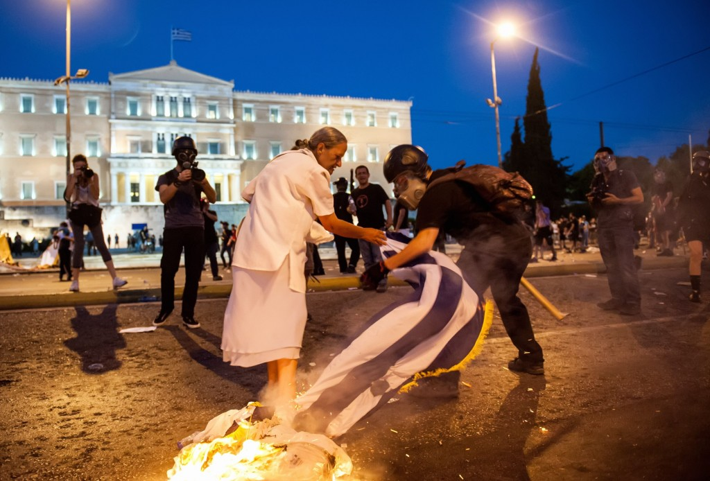 A woman attempts to stop a rioter from burning the Greek flag   © George Baboukos/Intime/Athen/REX/Shutterstock