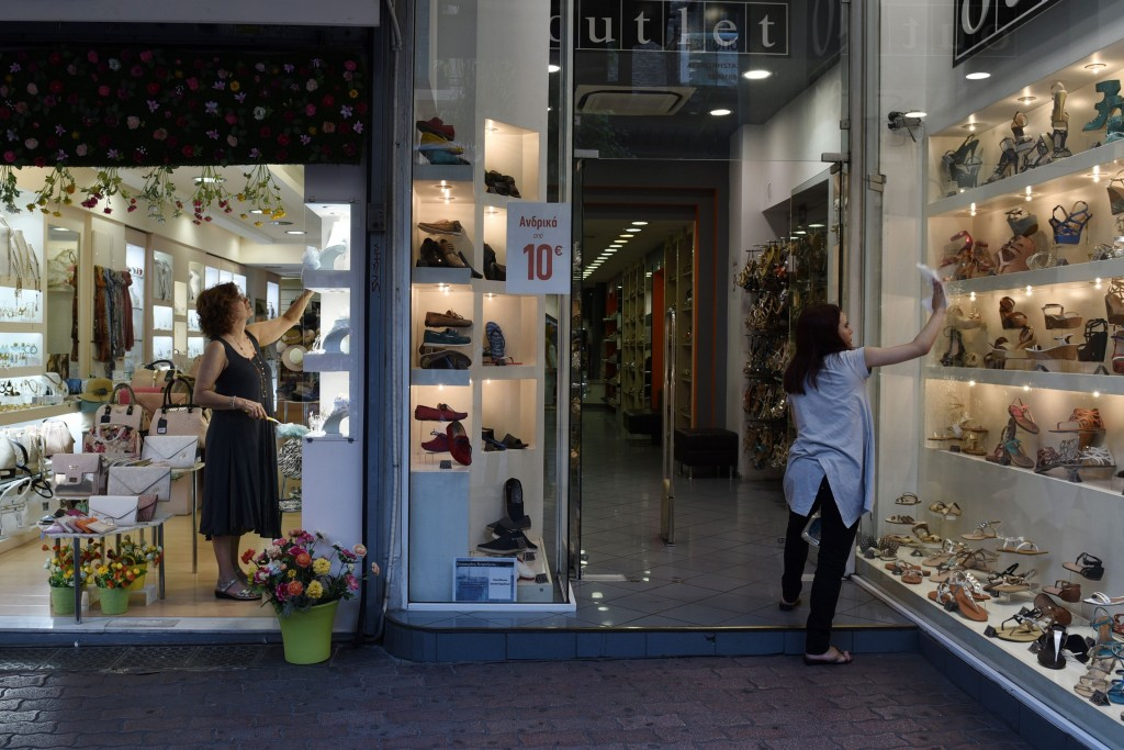 Two women clear the storefronts of their shops at Ermou Street, Athens   © Giannis Papanikos/AP/REX/Shutterstock