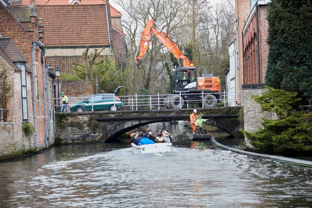 A boatload of tourists getting a front row seat to the installation of Bruges' unique pipeline | courtesy of De Halve Maan