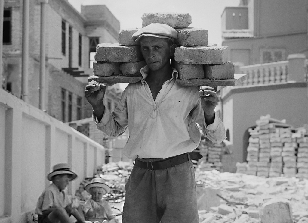 A Jewish worker carries bricks to build the first Hebrew city, Tel Aviv   American Colony Jerusalem / Wikimedia Commons