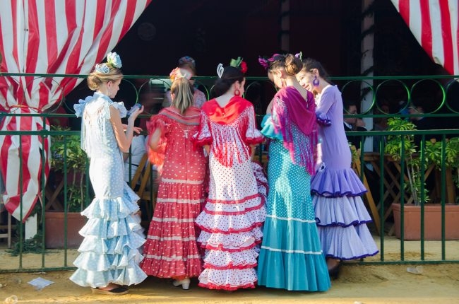 "<a href=""https://www.flickr.com/photos/vallausa/"">Women wearing traditional flamenco dress during Seville's April Fair | © Sandra Vallaure/Flickr</a>"