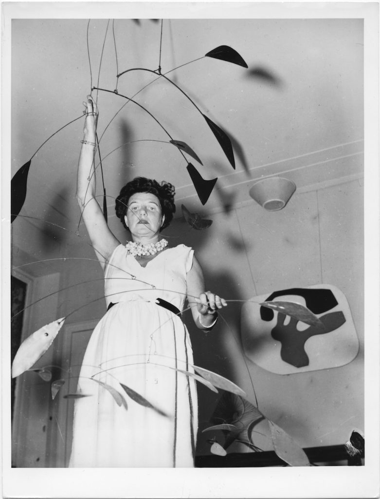 Peggy Guggenheim at Palazzo Venier dei Leoni with Alexander Calder, Arc of Petals (1941, PGC), Venice, early 1950s. Solomon R. Guggenheim Foundation. Photo Archivio CameraphotoEpoche. Gift, Cassa di Risparmio di Venezia, 2005 Behind her Jean Arp, Overturned Blue Shoe with Two Heels Under a Black Vault (1925, PGC).