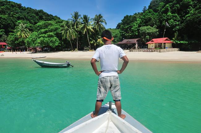 Local surveys the crystal clear water at Kapas island | © Izz Hazel
