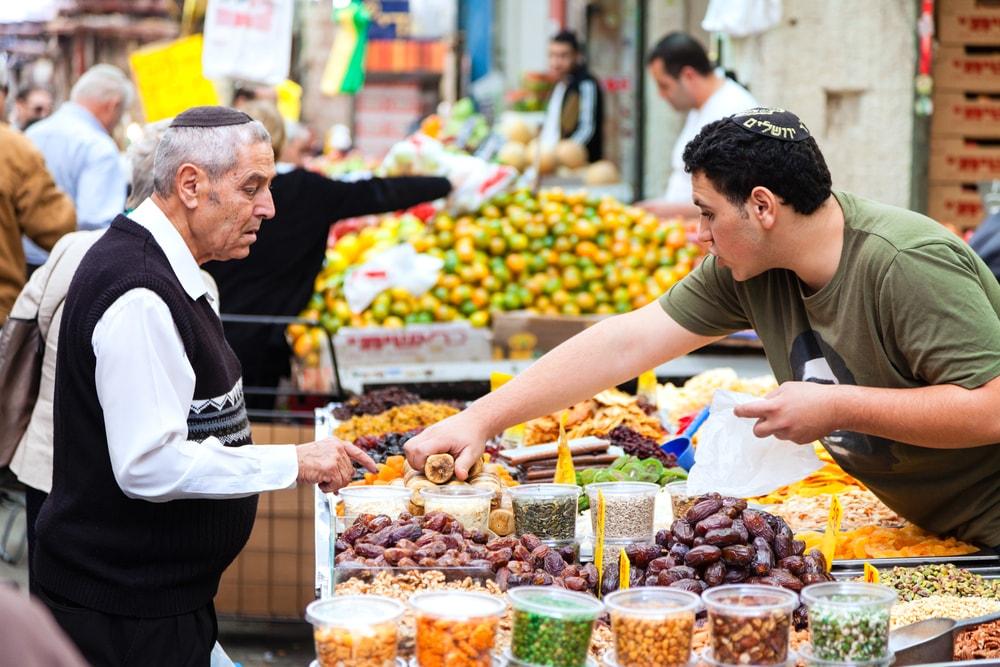 Buying goods at the Mahane Yehuda market, Jerusalem   © Alexey Stiop/Shutterstock