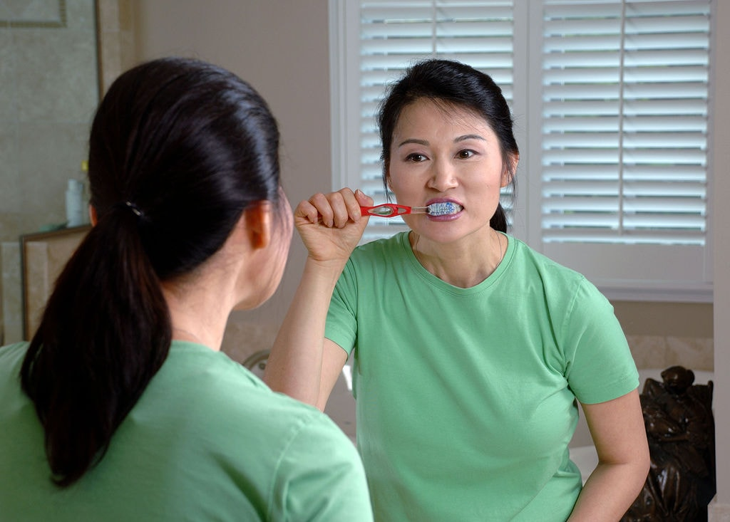 1024px-Woman_brushing_teeth
