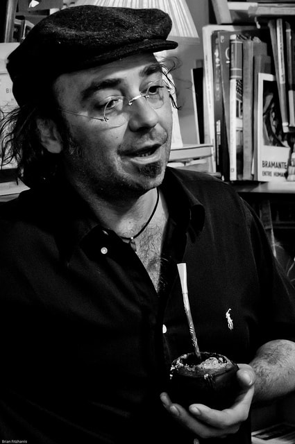 A Uruguayan man holding a mate beverage, in black and white