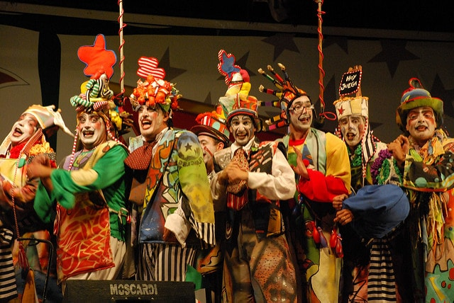 A Murga choir dressed in costume, performing on stage at Carnival