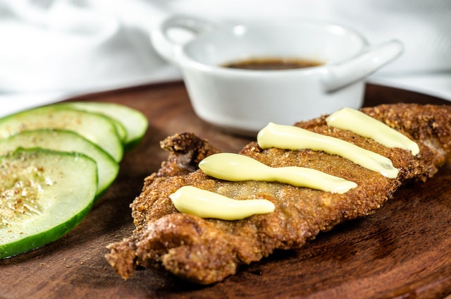 A milanesa with sauce and cucumber