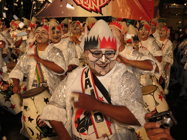 A group of drummers, dressed in costume, performing at a parade in Carnival