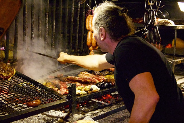 A man tending a grill with different cuts of meat