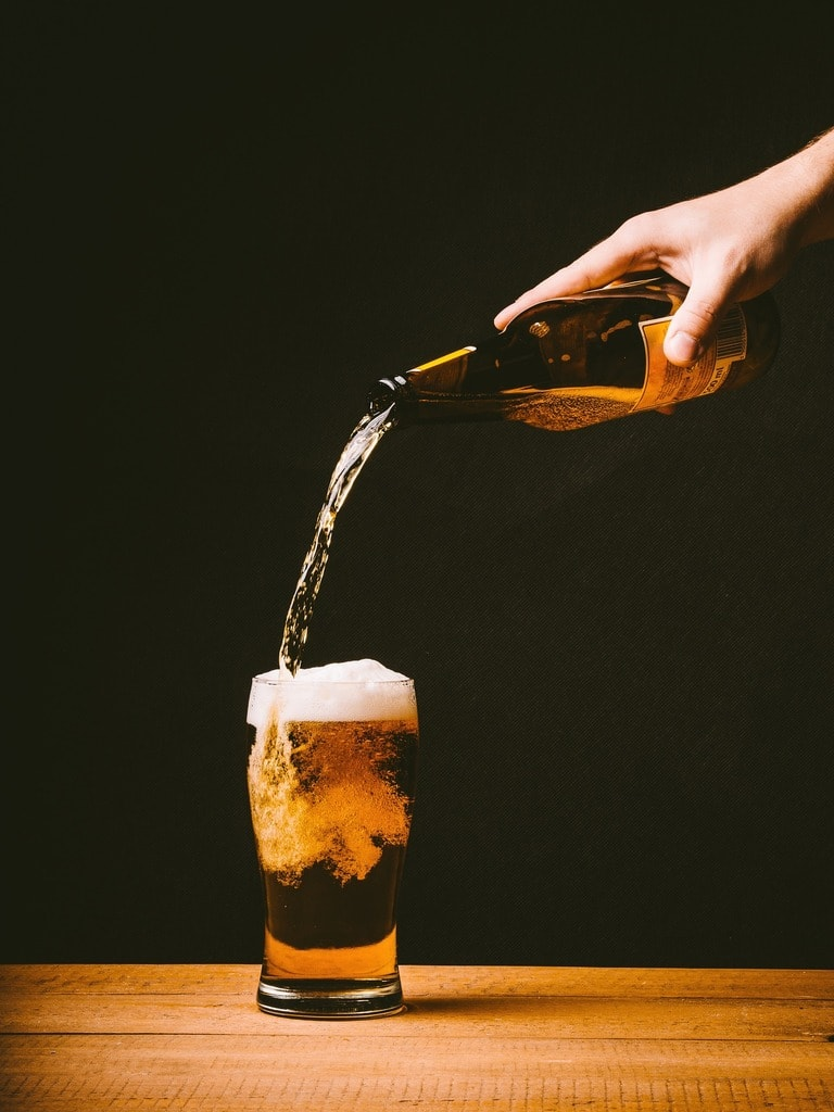 Someone pouring a pint of beer from a bottle