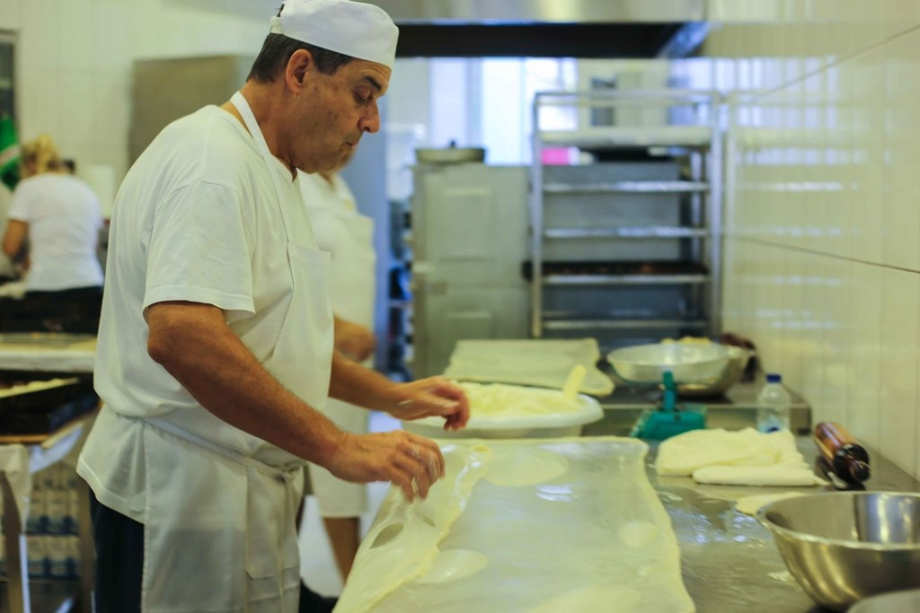 A baker gets the filo ready for their unique cheese filling | © Eleni Philippou