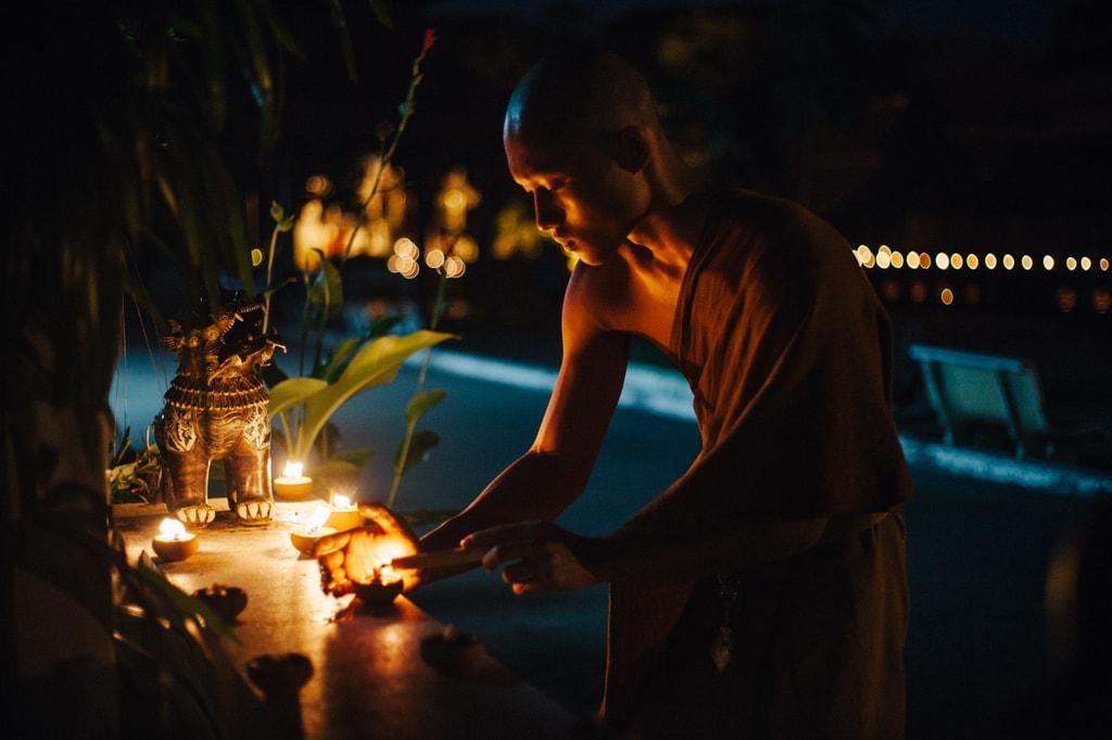 A monk lights a candle at a shrine | Gioia Emidi / © Culture Trip